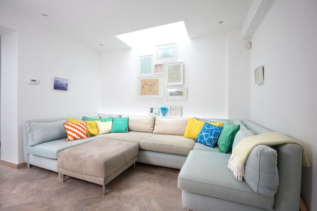 The seating unit in the cosy living area was specially made to fit the space. The artwork throughout is by Sarah herself.