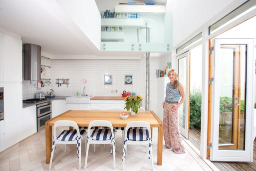 Sarah Lafferty in her innovative kitchen. Sarah almost doubled the size of her house by putting in a mezzanine, and added light with expanses of glass. Photo: Tony Gavin.