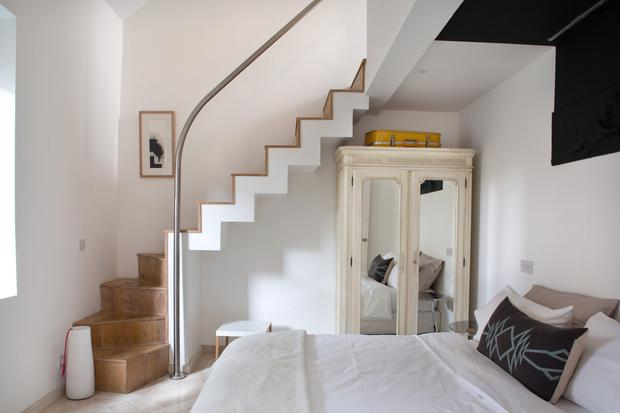 The cottage has two bedrooms to the front. There's underfloor heating on the ground level, including in Sarah's bedroom, which has a staircase to the mezzanine. The French-style wardrobe is one of the few relics that survived from the old house