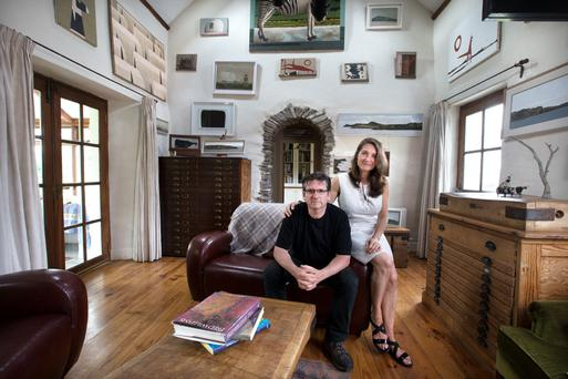 John and Christina in the living room, which is furnished in old pine and many examples of John's different painting periods. There are several butcher's blocks around the house. 'They remind me of the Australian landscape,' John notes. Photo: Tony Gavin