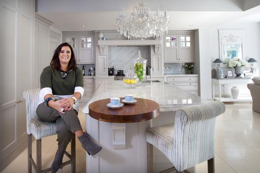Interior designer Jennifer Grace in her spectacular kitchen. She designed the units herself, which are made of poplar. Features include easy-close dovetailed drawers. The worktops are made of Carrara marble. Photo: Tony Gavin