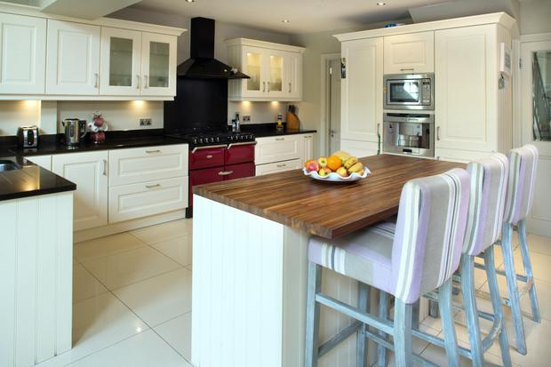 Careena opted for cream country-style kitchen units. She added drama by installing a red Stanley range.