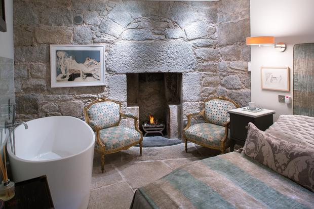 The bedroom features another Michael Farrell painting over the bath. The beautiful fabrics on the headboard designed by Simone, on the bed and on the chairs soften the effect of the stone walls