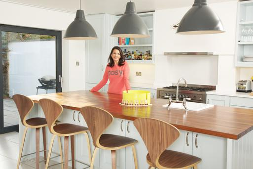 Entrepreneur Carol-Anne Leyden in her kitchen. The stools are Norman Cherner-style bar stools and the yellow fruit bowl is made with solid oak and metal