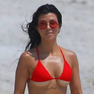Kourtney Kardashian in a red bikini takes a walk on the beach with her friends in Mexico. Picture: Splash News
