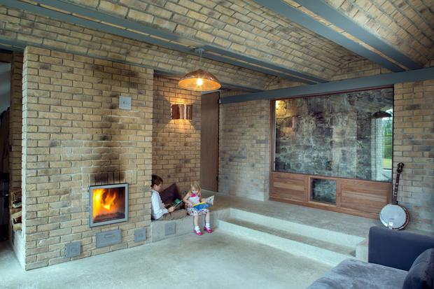 Daire's children, Tadgh and Aoibheann, on the steps - like a stage - of the music room. The masonry stove is built into the bricks. The window faces directly onto the wall of Phoenix Park and one of the front windows is reflected in the expanse of glass. The copper light fittings are made from a disused immersion heater