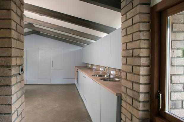 The kitchen is on the upper floor. The units, made of marine-ply sheeting, were built on site. Between the trusses and the ceiling there are windows to allow light in. The little light bricks just above the units are an interesting addition