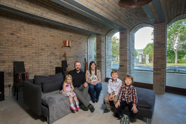Daire Bracken with his wife Eimear and their three children - Aoibheann, Tadgh and Liam - in the music room on the ground floor. The arched windows echo the curve of the pitch of the ceiling