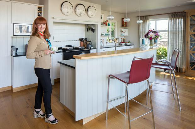 Interior designer Collette Ward in her kitchen with its high-backed island and black Aga.