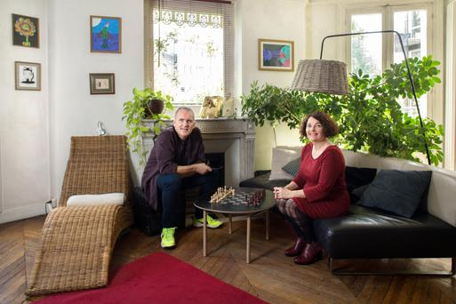 Motion-capture artists Denis and Anne in their spacious living room. The mantelpiece is original to the apartment, which is in a Haussmann building and dates from 1882. The artwork is by the couple and their twin girls, Bo and Lottie. The helmet on the mantlepiece is the Cyclops Helmet from their exhibition 'Bizarro' at Saint-Germain-des-Pres in September 2016
