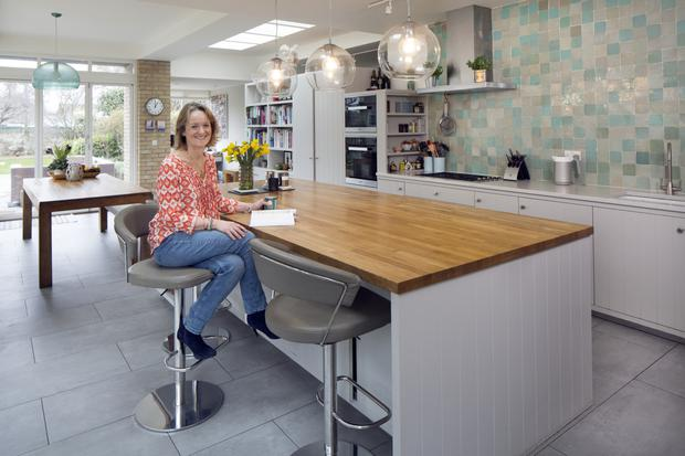 Writer Kate O'Brien in her kitchen, which is furnished with units made by Newcastle Design. She loves the extra-large island, and the tiled wall behind the hob and sink.