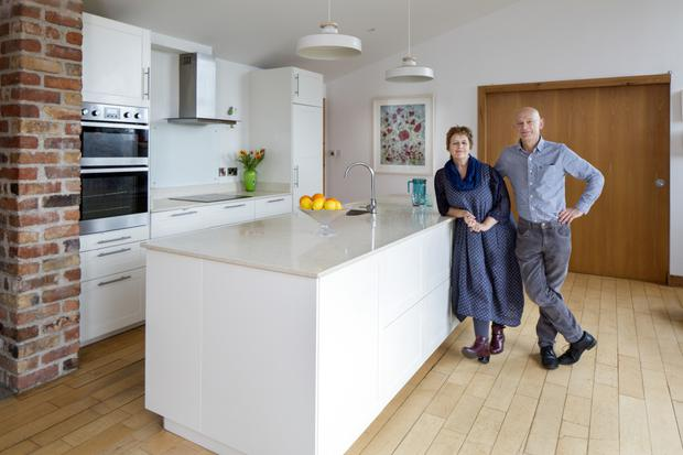 Miriam and Ronan in their light-filled kitchen. The units, from Ikea, have quartz worktops. The picture of poppies is one of Miriam's felt works