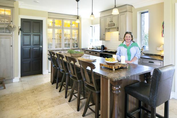 Marita Varley in the open-plan kitchen. The granite is local, but all the units are from Home Depot in the United States and the lighting is from Restoration Hardware there