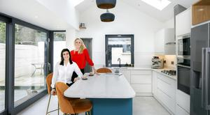 Simona and Joy (wearing red) in the kitchen, which is in the high-ceilinged, light-filled extension designed by architect Noel Kerley. The interior was designed by Tullio Orlandi, who went for lots of pops of bright colour.