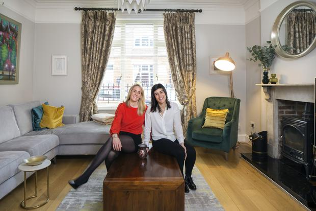Joy and Simona in the living room with its high ceiling and original windows and mantlepiece. Cushions of blue and gold add interest to the muted colour palette.The colourful painting over the sofa was a Christmas gift from Joy to Simona.