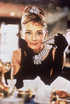 Hepburn in that black, shoulderless dress, matching gloves, and a tiara, smiles with a cigarette holder in her hand, in the film, 'Breakfast at Tiffany's'