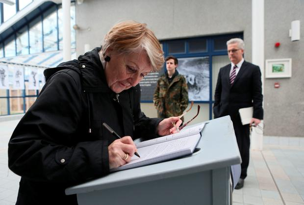 A woman signs the book of condolence in Limerick. Photo: PA