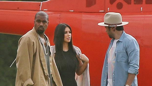 Kanye West and Kim Kardashian speak to an unidentified friend as they arrive by helicopter at the Glastonbury music festival (Joel Ryan/Invision/AP)