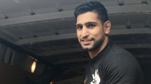 World champion boxer Amir Khan has personally distributed aid to Syrian refugees in Greece
