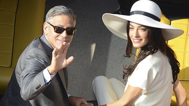 George Clooney and his wife Amal Alamuddin leave the city hall after their civil marriage ceremony in Venice, Italy