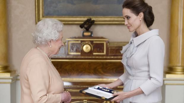 Angelina Jolie is presented with her honorary damehood by the Queen