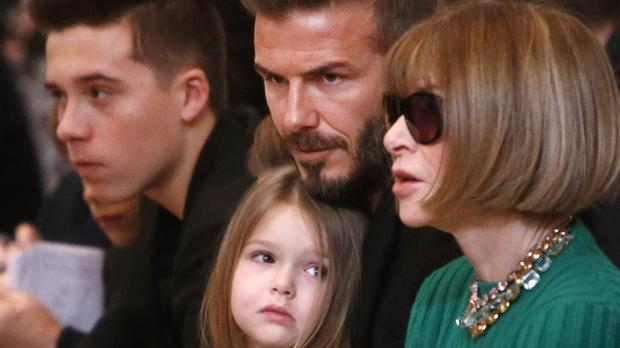 David Beckham, centre, sits in the front row next to Anna Wintour, right, along with his son, Brooklyn, left, and daughter, Harper, before the Victoria Beckham Fall 2015 collection show during Fashion Week in New York. (AP)
