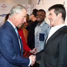 The Prince of Wales meets Simon Cowell, right, during the awards ceremony
