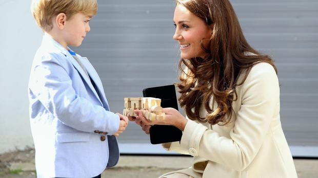 Kate is presented with a train for Prince George by actor Oliver Barker