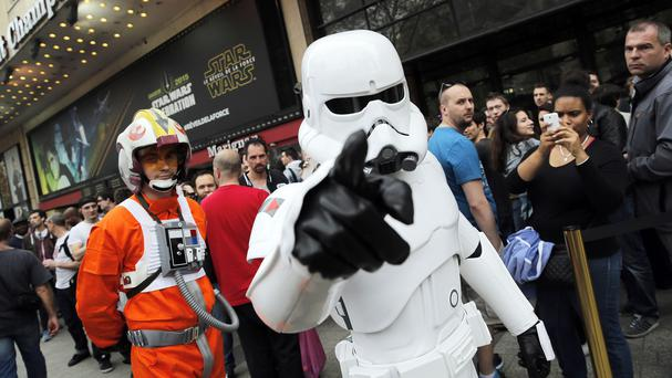A man dressed as a Stormtrooper walks past people in Paris, France, as they queue to attend the streaming of Star Wars Celebration from the Anaheim Convention Centre in California (AP)