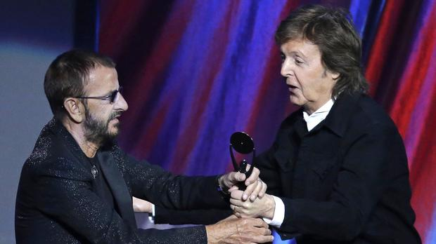 Sir Paul McCartney hands the trophy to Ringo Starr at the Rock and Roll Hall of Fame Induction Ceremony (AP)
