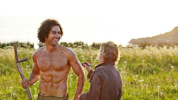 Poldark star Aidan Turner gets the brush-off from a crew member in this behind-the-scenes shot from the BBC costume drama (BBC/PA)