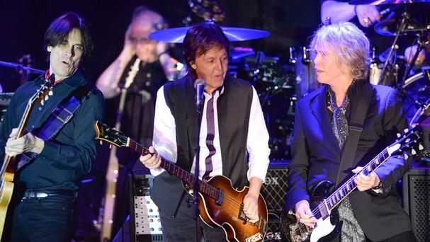 Paul McCartney, centre, played a private concert with a crowd that included Wall Street executives and celebrities including Sting and Oprah (AP)