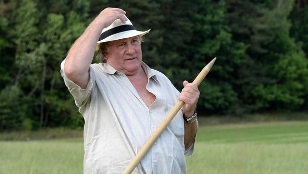 French actor Gerard Depardieu holds a hand scythe in the presidential residence of Ozerny, outside Minsk, Belarus (AP)