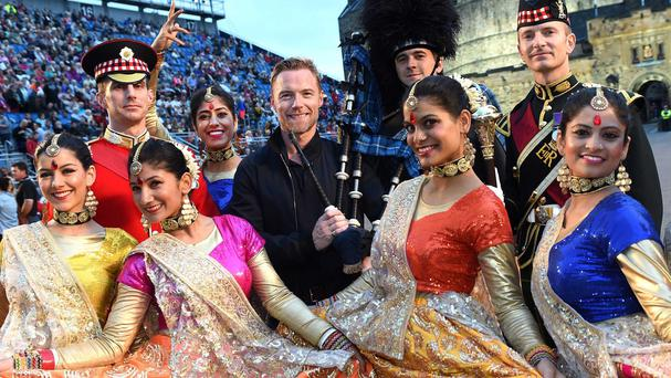 Ronan Keating meets members of the Bollywood dance troupe, plus Garrison Sergeant Major and Tattoo Regimental Sergeant Major John Ford, Drum Major Mick Hay and Lone Piper Corporal Stuart Hunter (The Royal Edinburgh Military Tattoo/PA Wire)