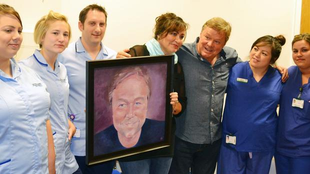 Ted Robbins with his sister Jane Robbins, centre, who painted a portrait of him, and staff from the hospital's cardiothoracic critical care unit in Manchester (Wythenshawe Hospital/PA)