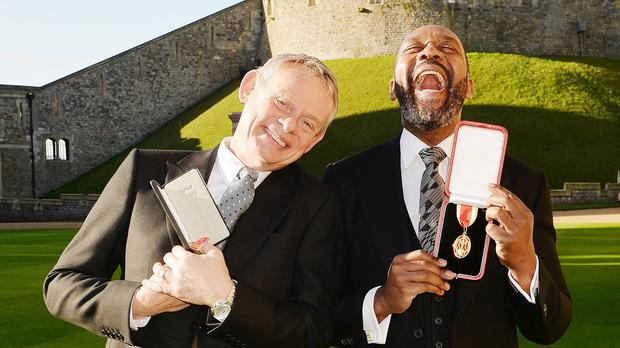 Martin Clunes, left, shares a laugh with Sir Lenny Henry after their investiture ceremony at Windsor Castle