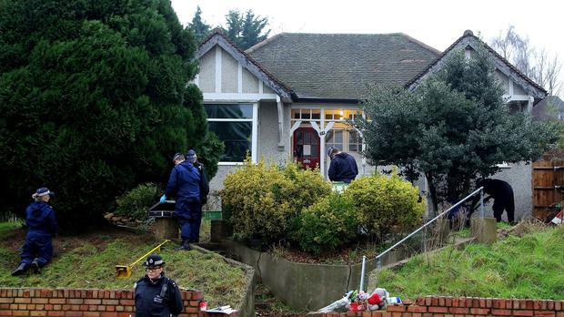 Police officers search the front garden of the house in Erith, Kent