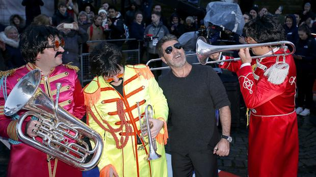 David Walliams, dressed in a Beatles costume, plays the trumpet as Simon Cowell arrives at the Britain's Got Talent auditions 2016 held at Liverpool's Empire Theatre (Pete Byrne/PA Wire)