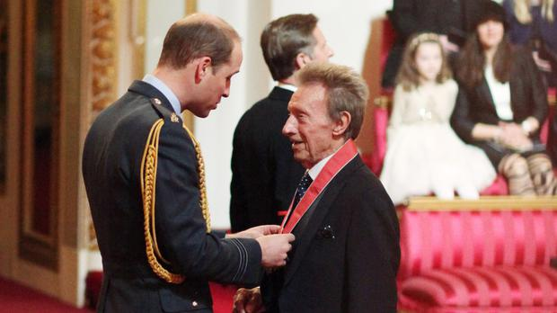 Former Scotland and Manchester United football great Denis Law is made a CBE by the Duke of Cambridge at an Investiture ceremony in Buckingham Palace