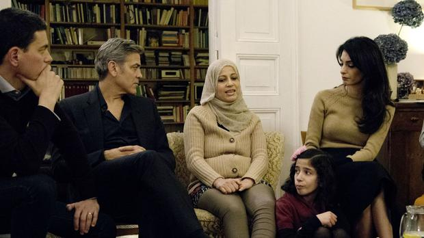 David Miliband, George Clooney and Amal Clooney listen to the experiences of the refugees