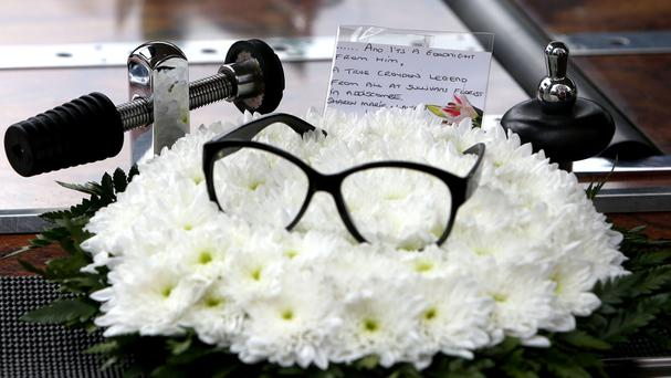 A pair of glasses rest on flowers left in tribute to Corbett