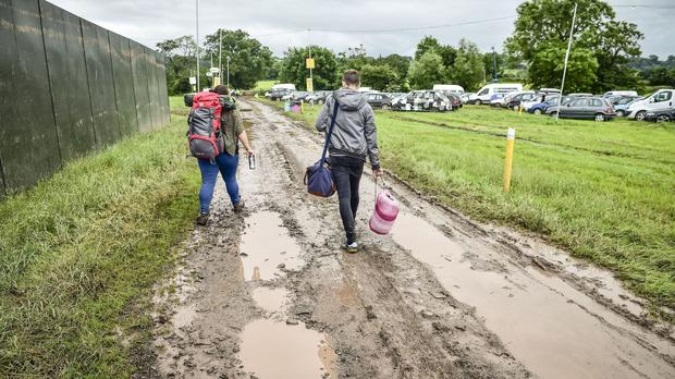 People traverse muddy and waterlogged fields and paths at Glastonbury Festival