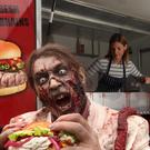 Zombie Ashley Siberini tucks into a brain burger at London's The Gory Gourmet food stall to promote the launch of The Walking Dead Season 2 on DVD and Blu-ray