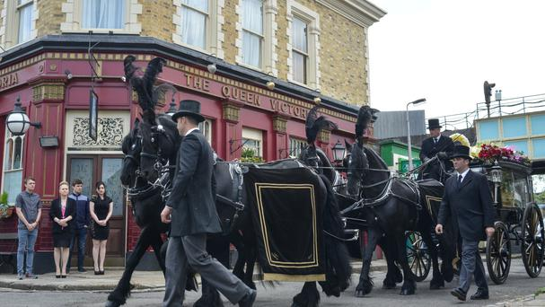 Peggy Mitchell's funeral procession passes the Queen Vic