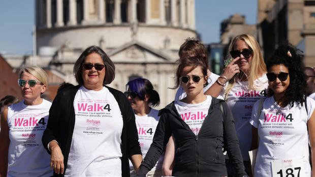 Helena Bonham Carter and Sandra Horley, chief executive of Refuge, join survivors and supporters walking across Millennium Bridge, London