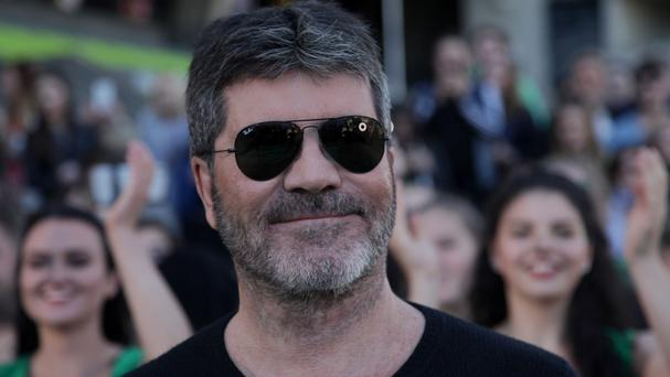 Simon Cowell has sarcastically apologised to One Direction for making them mega stars.