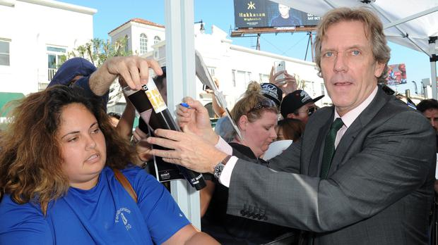 Hugh Laurie signs autographs for fans at a ceremony honoring him with a star on the Hollywood Walk of Fame on Tuesday, Oct. 25, 2016, in Los Angeles. (Photo by Richard Shotwell/Invision/AP)