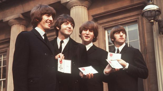 The Beatles at Buckingham Palace after collecting their MBEs
