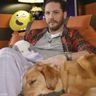 Tom Hardy as he cuddles up to his dog for his new role - as a bedtime storyteller on CBeebies (BBC/PA)