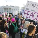 Women's March demonstrators walk past the White House in Washington
